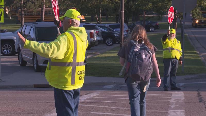 Two crossing guards help a student cross Stewart Avenue outside of John Muir Middle School in...
