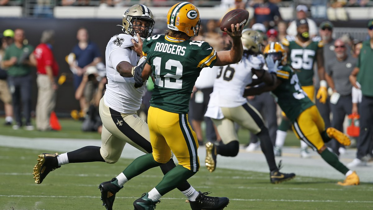 Green Bay Packers quarterback Aaron Rodgers (12) is his by New Orleans Saints defensive end...