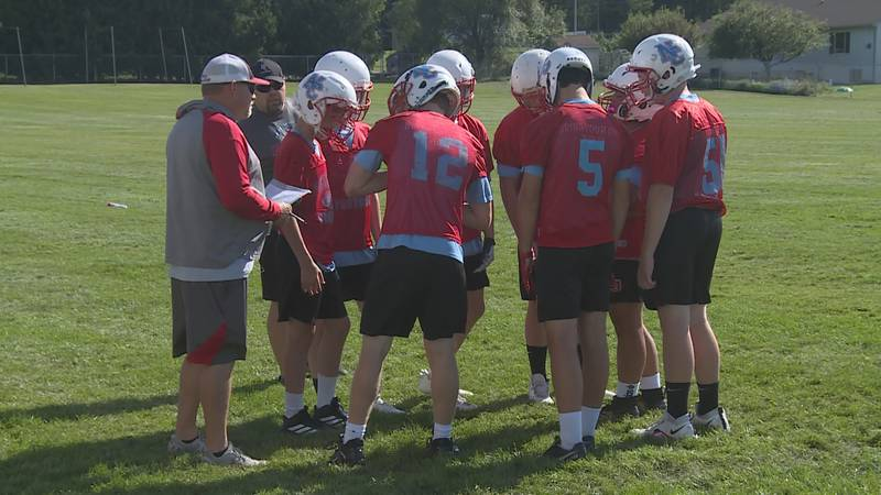 Newman Catholic head coach Paul Michlig in the huddle with his team on August 12, 2021.
