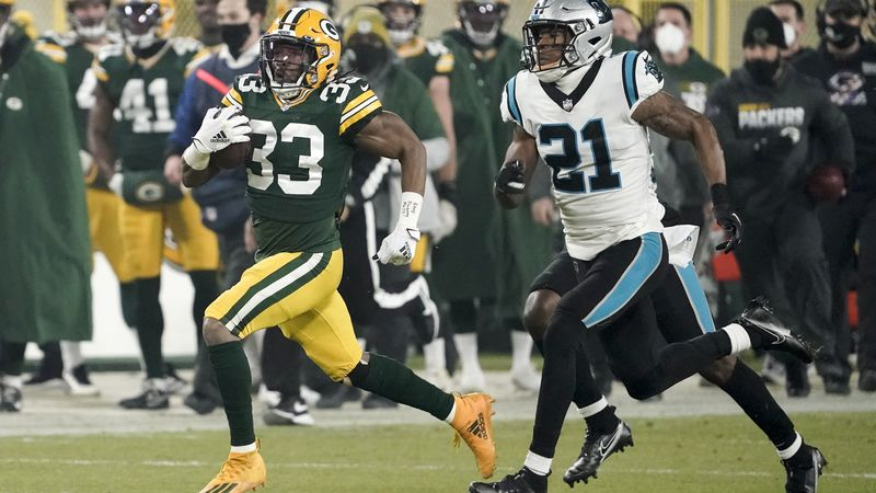 Green Bay Packers' Aaron Jones runs past Carolina Panthers' Jeremy Chinn during the first half...