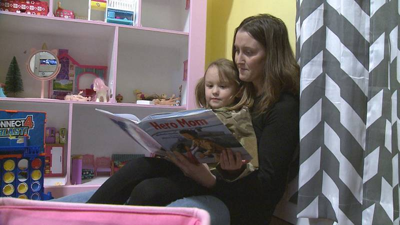 Mandi Chojnacki reads to her daughter Liberty.