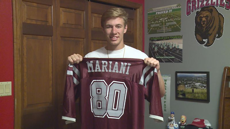 Rhinelander graduate and Montana Football commit Quinn Lamers holding up the jersey of his...