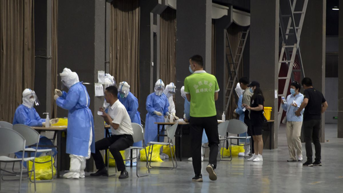 Workers in protective suits administer coronavirus tests at a COVID-19 testing site for those who were potentially exposed to the coronavirus at a wholesale food market in Beijing, Wednesday, June 17, 2020. (AP Photo/Mark Schiefelbein)