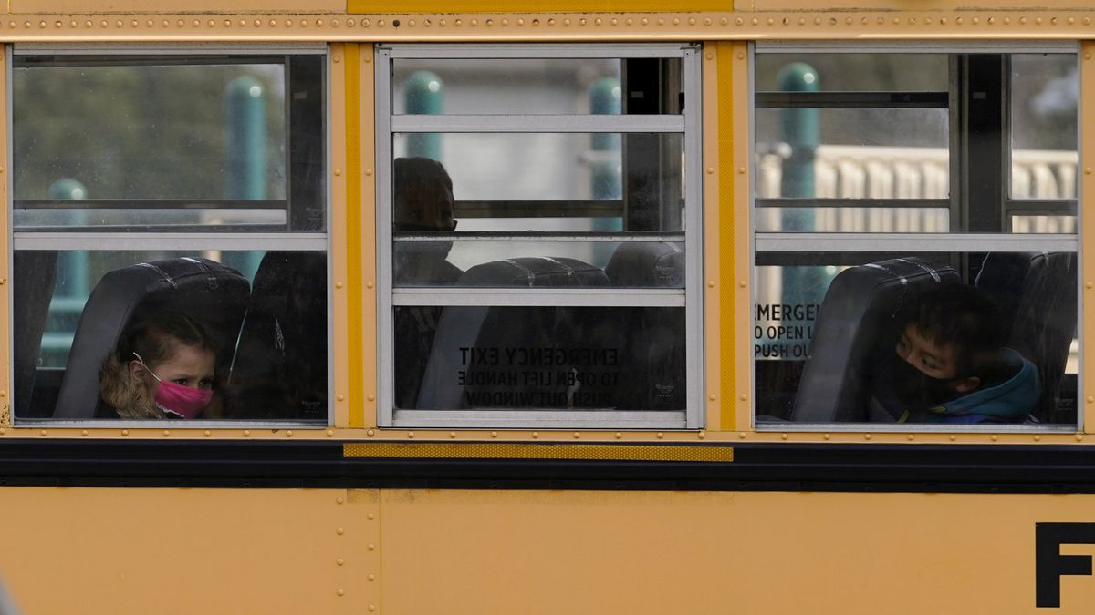 Elementary school students sit on board a school bus after attending in-person classes at...