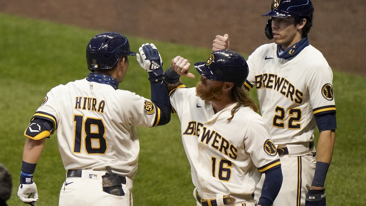 Milwaukee Brewers' Keston Hiura is congratulated by Ben Gamel (16) and Christian Yelich (22)...