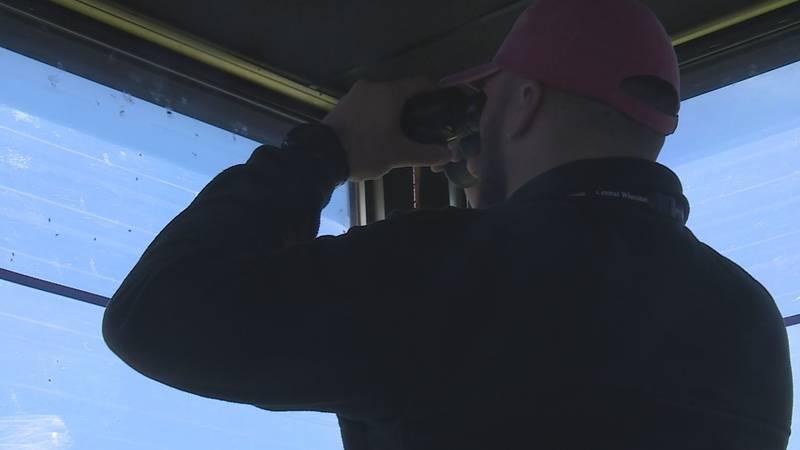 Keegan Korbol uses binoculars to watch the runway at the Central Wisconsin Airport.