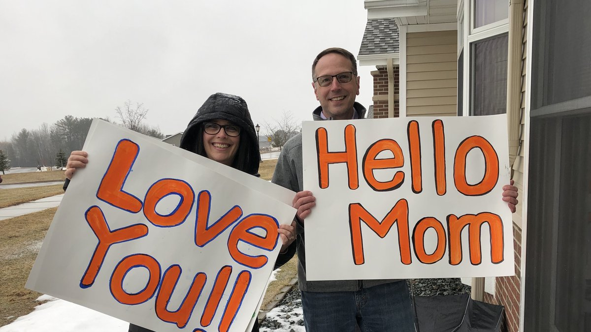 Mark Michlig and Sara Helmer hold up the signs made for their mother at Rennes Health and Rehab...