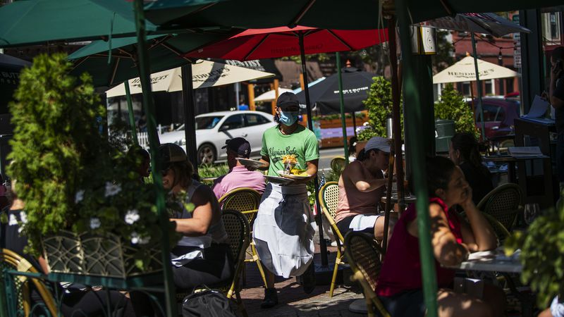 A waiter in a face mask delivers food to the tables outside of a local restaurant during lunch...