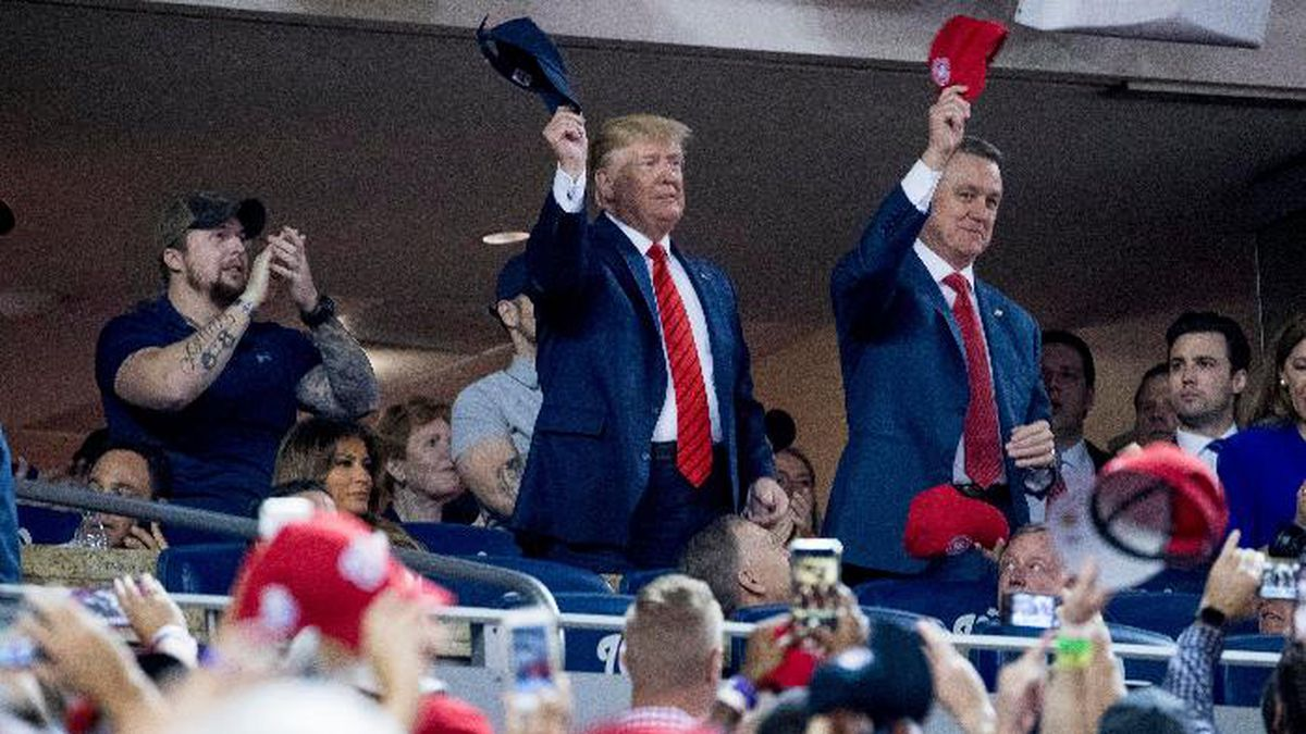 President Donald Trump, center, accompanied by Sen. David Perdue, R-Ga., right, and a member of the military, left, stands as members of the military are recognized during Game 5 of a baseball World Series between the Houston Astros and the Washington Nationals at Nationals Park in Washington, Sunday, Oct. 27, 2019. (AP Photo/Andrew Harnik)