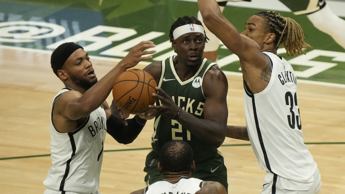 Milwaukee Bucks' Jrue Holiday tries to drive in traffic during the first half of Game 3 of the...