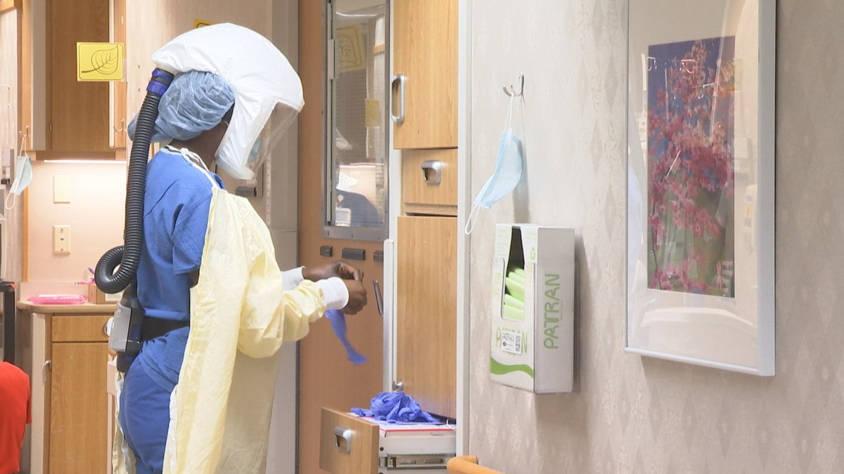 A health care worker puts on PPE to head into a COVID patient's room.