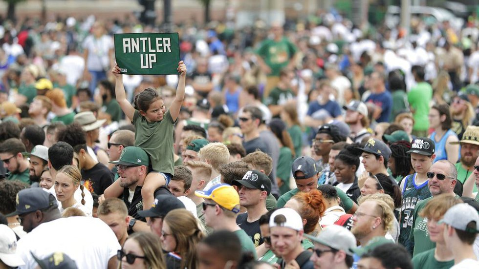 A fan holds up a sign during a parade celebrating the Milwaukee Bucks' NBA Championship...