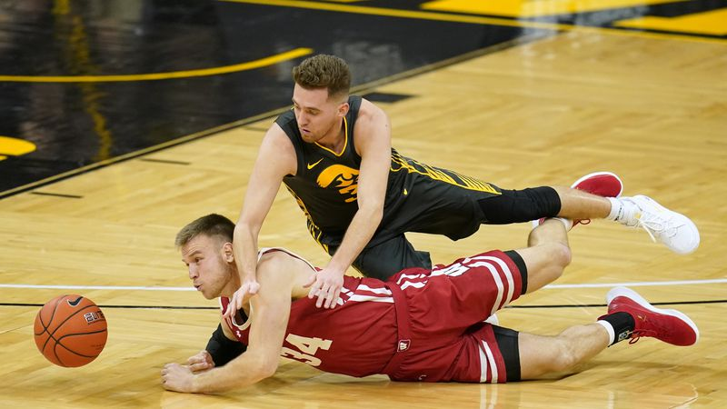 Wisconsin guard Brad Davison (34) fights for a loose ball with Iowa guard Jordan Bohannon...