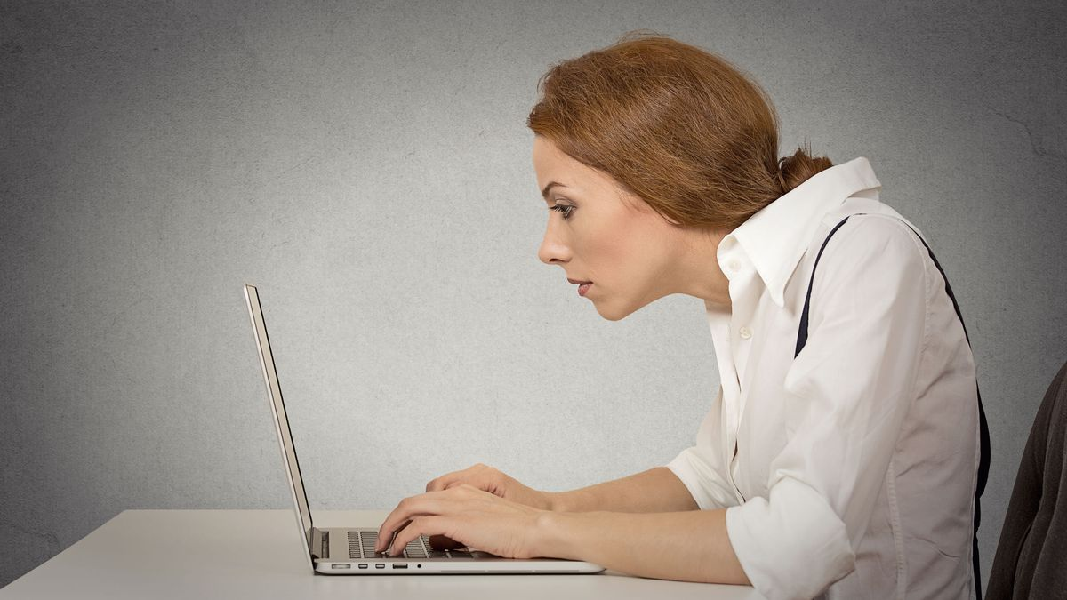 Young woman working on computer sitting at desk isolated on grey wall gloomy office background...