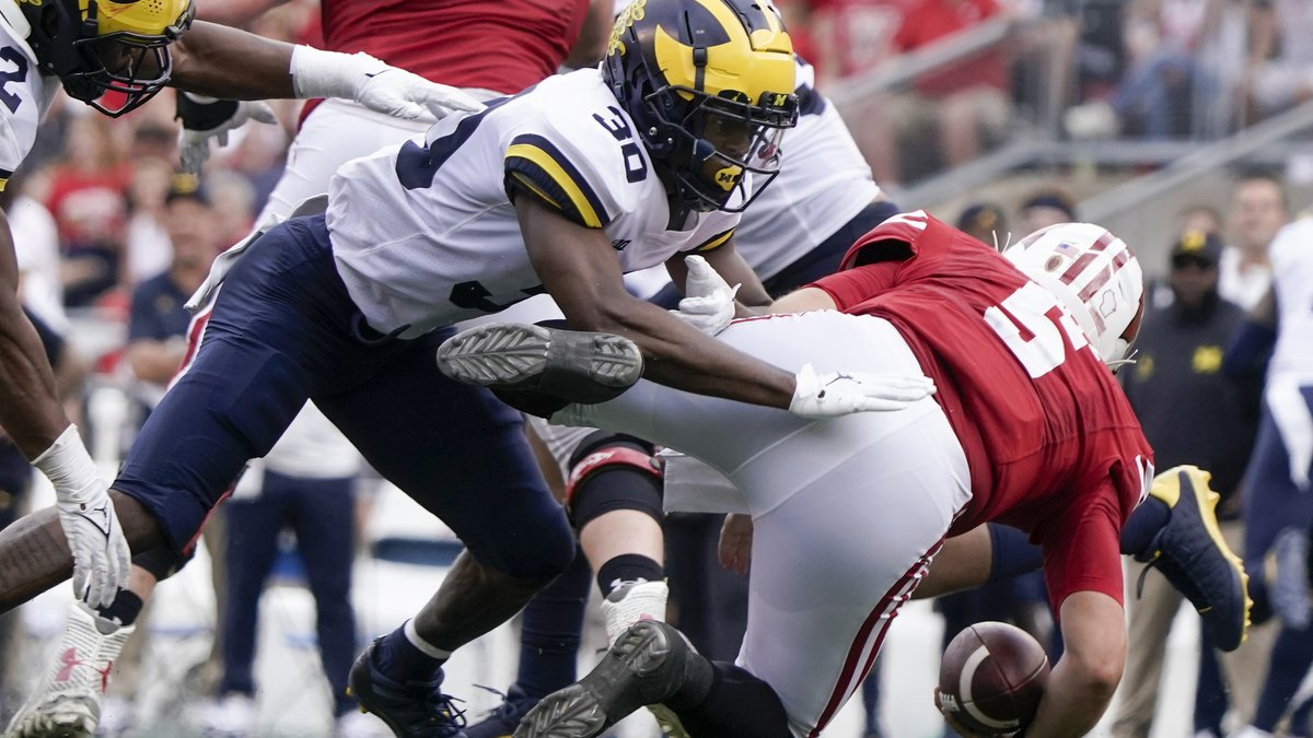 Michigan's Daxton Hill hits Wisconsin's Graham Mertz during the second half of an NCAA college...