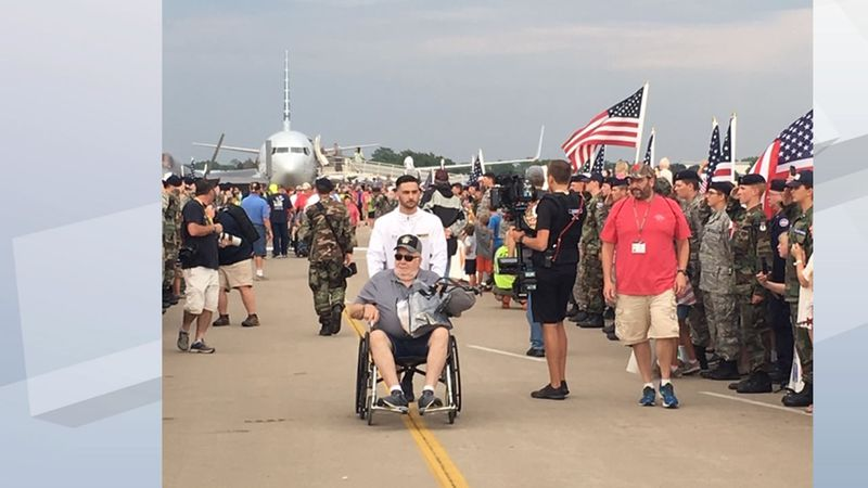 A crowd of thousands at EAA AirVenture greets 115 Vietnam veterans on an Old Glory Honor Flight...