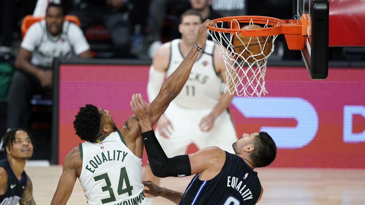Milwaukee Bucks' Giannis Antetokounmpo (34) dunks the ball over Orlando Magic's Nikola Vucevic (9) during the second half of an NBA basketball first round playoff game Monday, Aug. 24, 2020, in Lake Buena Vista, Fla.