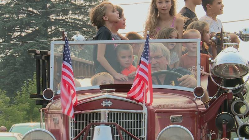 People from Edgar, Wi. take a ride in an old-fashioned firetruck.