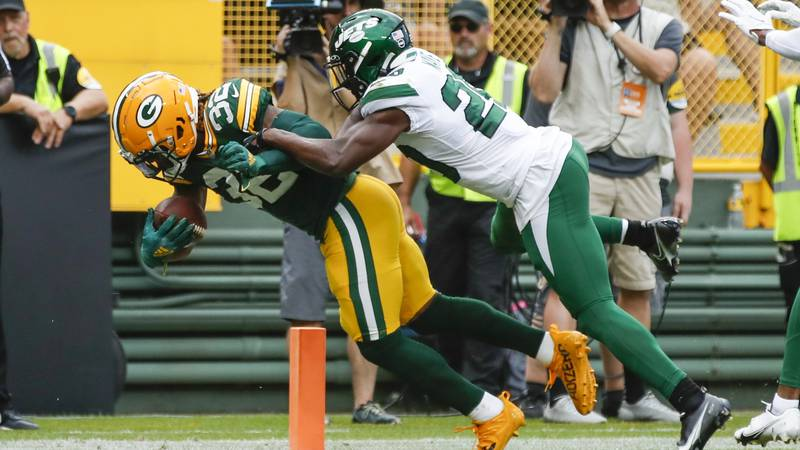 Green Bay Packers' Kylin Hill runs past New York Jets' Marcus Maye for a touchdown during the...