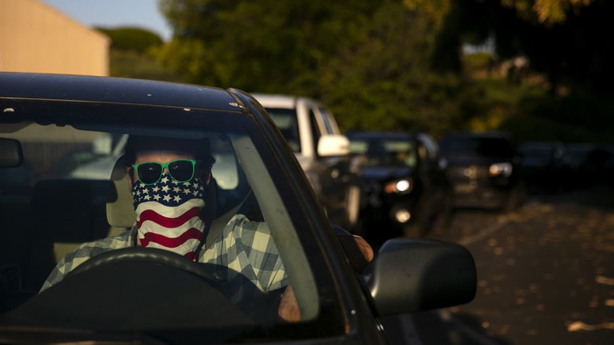 Charles McNulty wears a face covering while waiting in his car to purchase a movie ticket at...