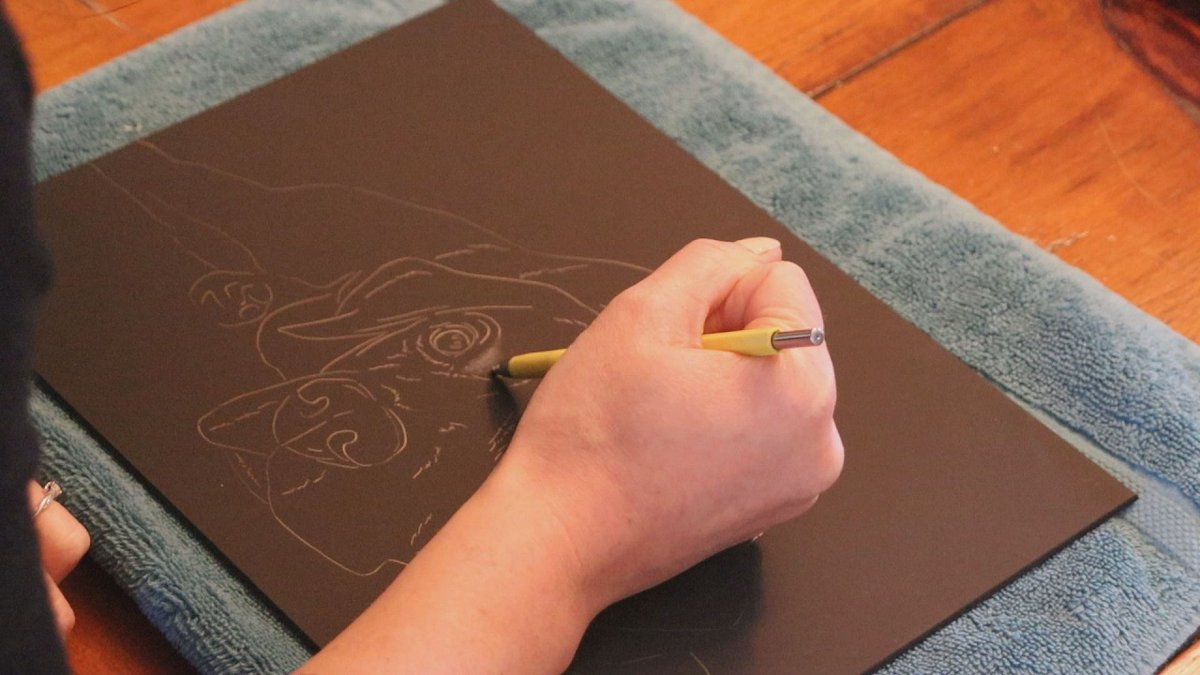Scratchboard artist Melissa Mason works on a project while at home on quarantine on March 17,...