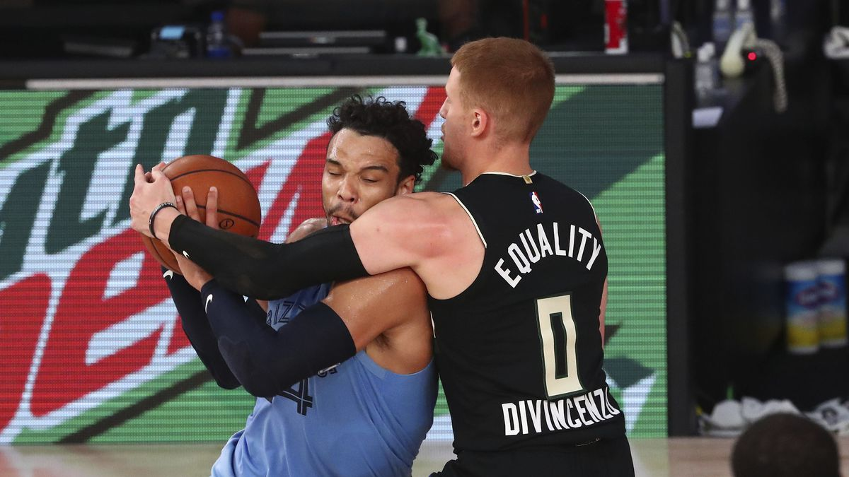 Milwaukee Bucks guard Donte DiVincenzo (0) defends against Memphis Grizzlies guard Dillon Brooks (24) in the first half of an NBA basketball game Thursday, Aug. 13, 2020, in Lake Buena Vista, Fla. (Kim Klement/Pool Photo via AP)