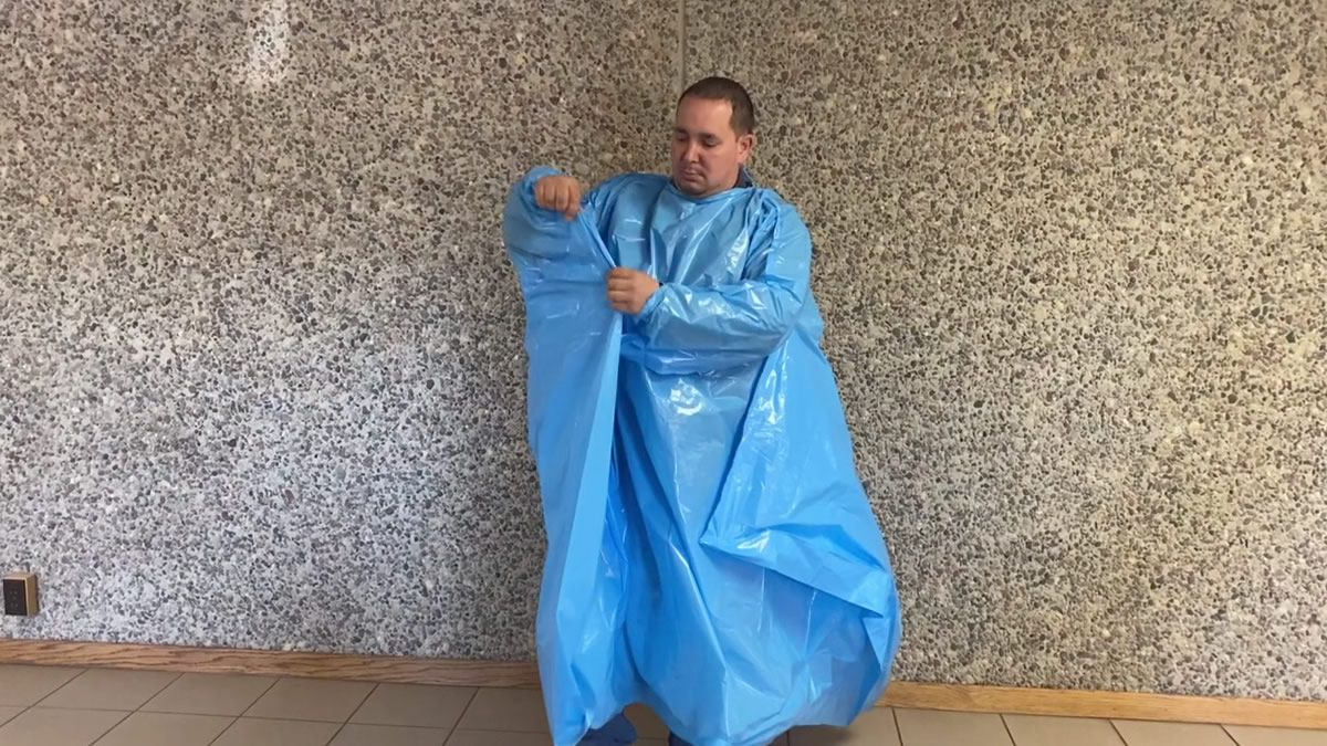 Demonstration of the Norolex protective gown. The Shawano manufacturer retooled equipment to...