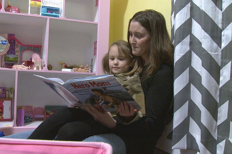 Mandi Chojnacki reads to her daughter Liberty.