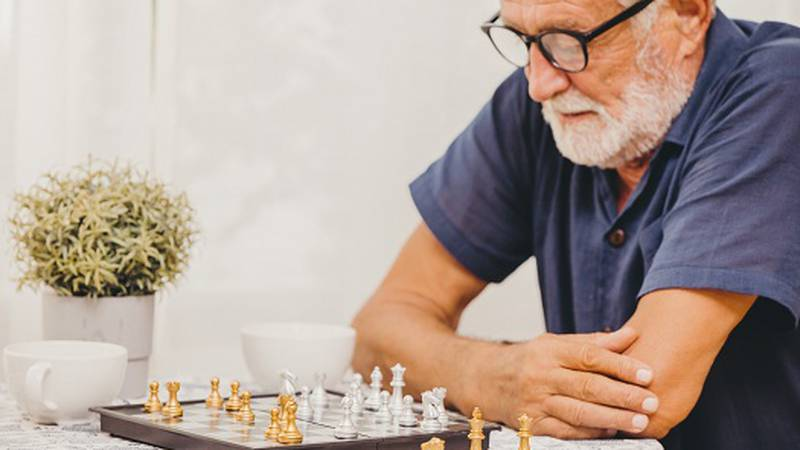 Smart Elder playing Chess board game at home for training brain memory and thinking happy...
