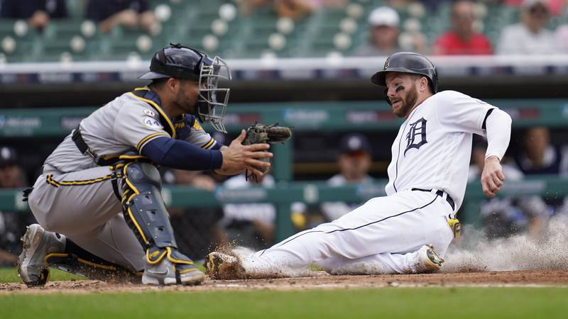 Detroit Tigers' Robbie Grossman, right, slides safely into home plate to score as Milwaukee...