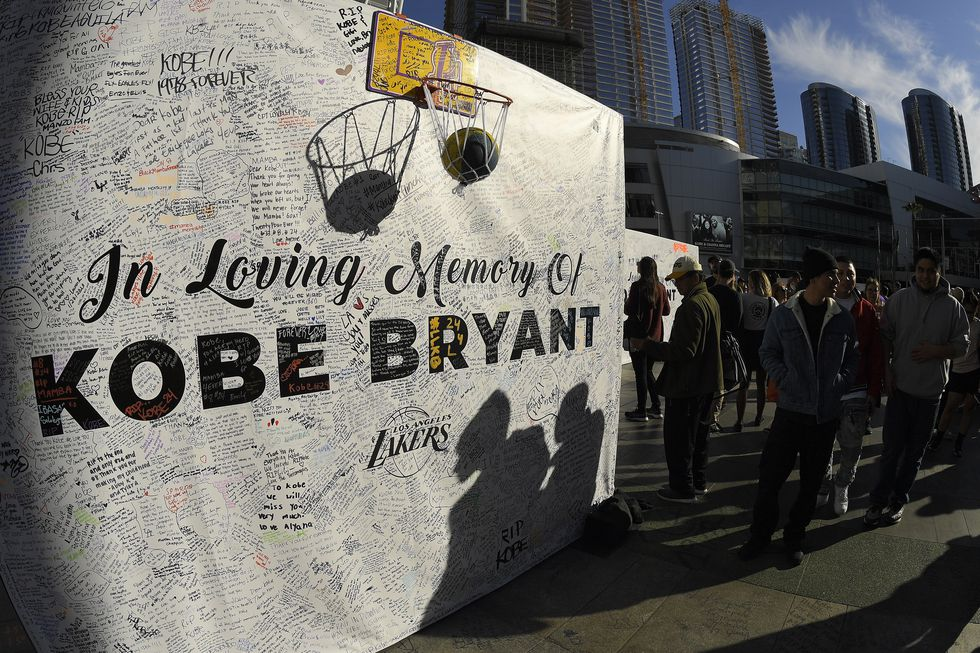 FILE - In this Jan. 28, 2020, file photo, shadows are cast on a memorial wall as fans gather at...