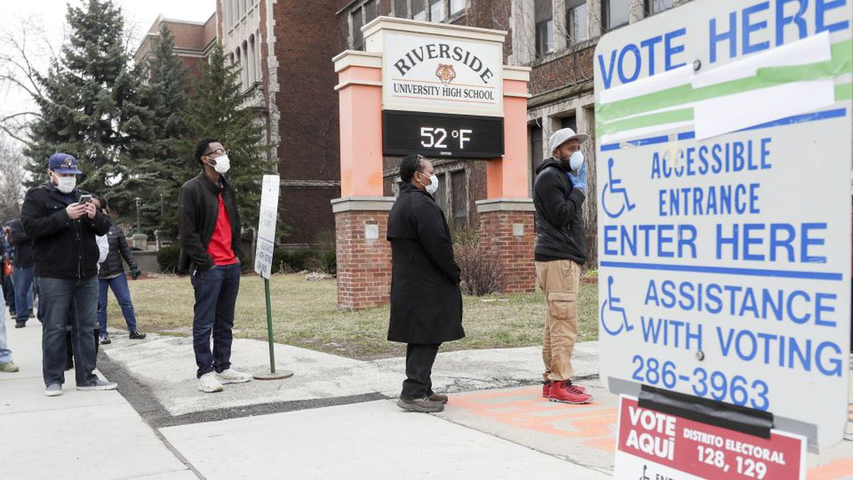 Voters line up at Riverside High School for Wisconsin's primary election Tuesday April 7, 2020, in Milwaukee. The new coronavirus causes mild or moderate symptoms for most people, but for some, especially older adults and people with existing health problems, it can cause more severe illness or death. (AP Photo/Morry Gash)