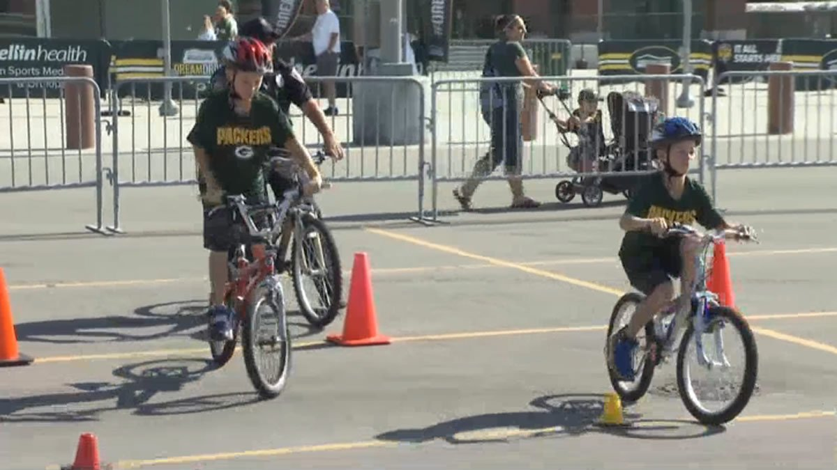 Kids ride bikes through an obstacle course outside Lambeau Field during a bike safety rodeo at...
