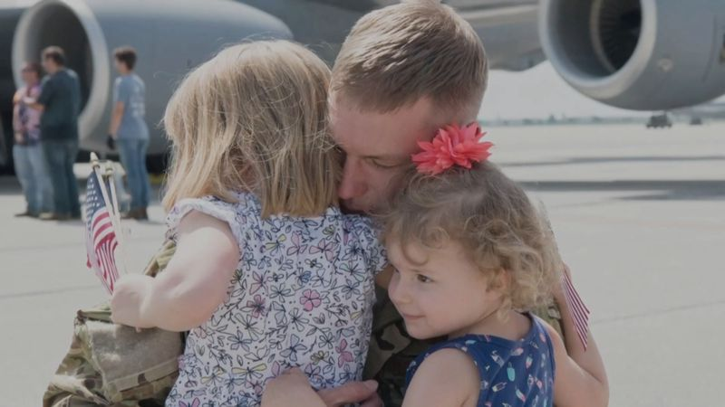 Military children greet and hug their dad