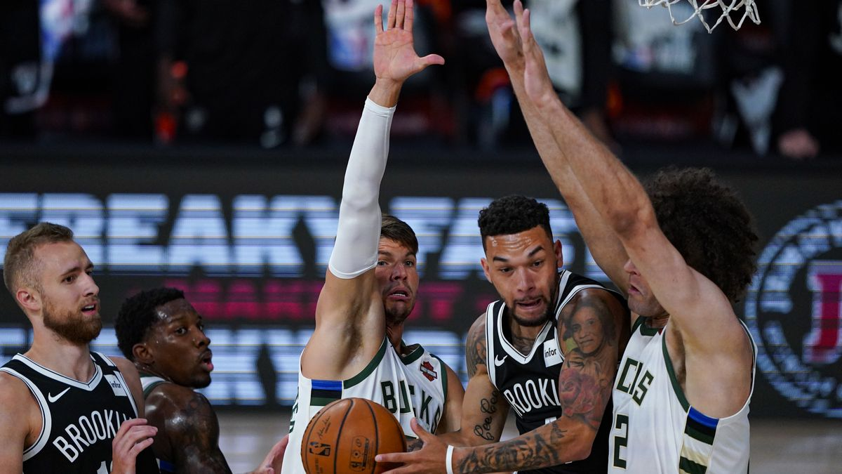 Brooklyn Nets guard Chris Chiozza (4) cuts between Milwaukee Bucks guard Kyle Korver (26) and center Robin Lopez (42) during the first half of an NBA basketball game Tuesday, Aug. 4, 2020 in Lake Buena Vista, Fla. (AP Photo/Ashley Landis)