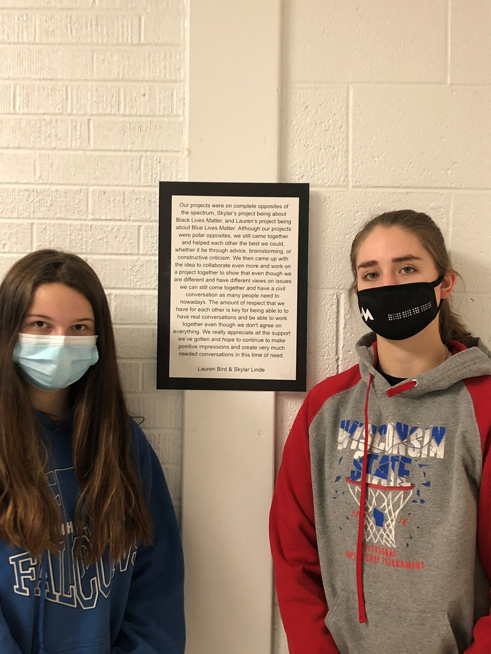 Lauren Bird (right) and Skylar Linde (left) pose in front of the explanation they wrote about...