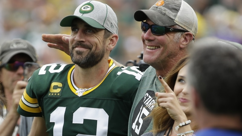 Green Bay Packers' Aaron Rodgers smiles with former quarterback Brett Favre during halftime of...