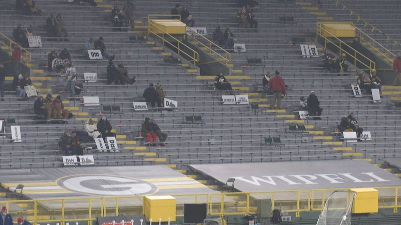 Front line workers sit in socially distanced groups at a Green Bay Packers game at Lambeau Field.