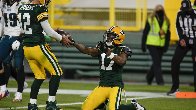 Green Bay Packers' Davante Adams gives quarterback Aaron Rodgers the ball after catching a...
