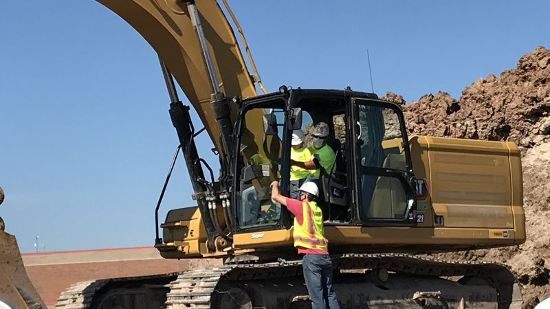 Five year old Dominic Filippini operates a backhoe with a construction worker during his...