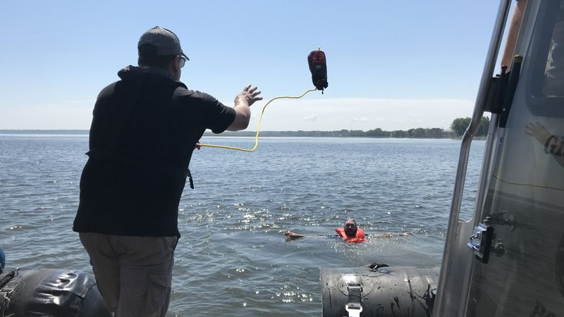 """A deputy throws a rope line to a """"victim"""" during boat patrol training."""