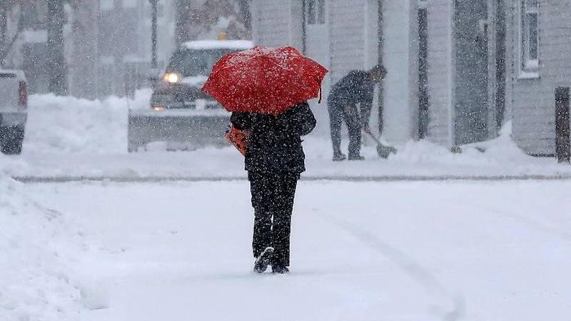 A pedestrian uses an umbrella while making their way down a snow-covered street, Tuesday, Dec....
