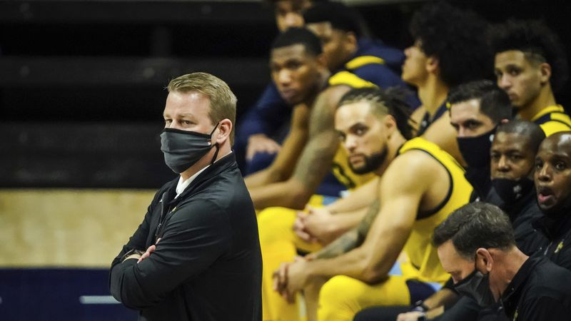 Marquette head coach Steve Wojciechowski (left) watches from the sideline during the second...