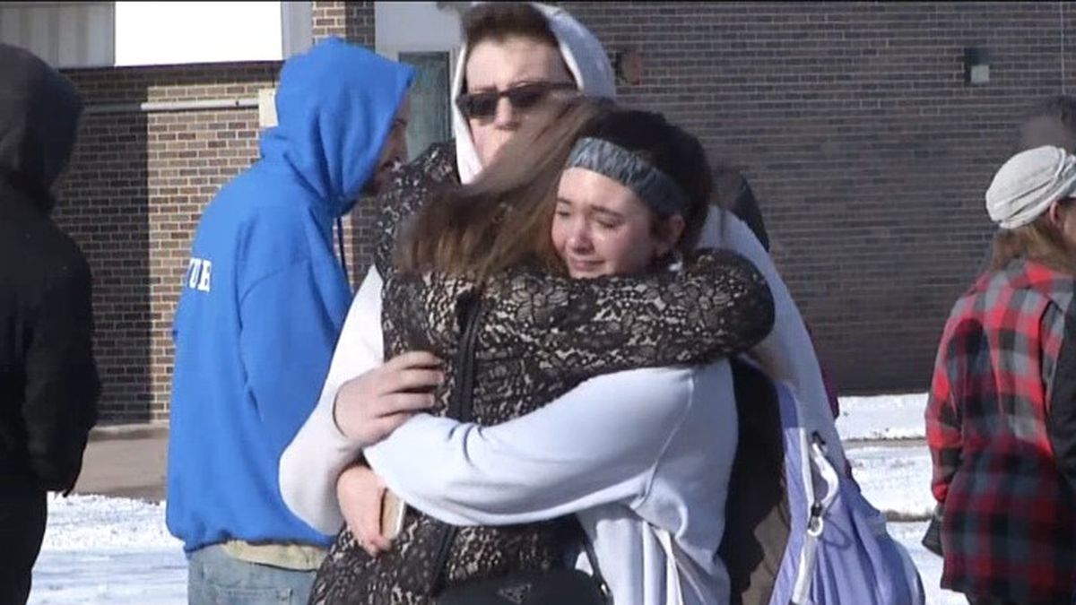 Parents and children hug each other as they are re-united after a stabbing and shooting at Oshkosh West High School. (WBAY Photo)