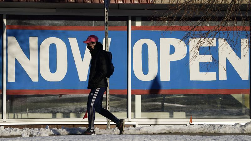 FILE - In this Feb. 25, 2021, file photo, a pedestrian in a face covering walks past the sign...