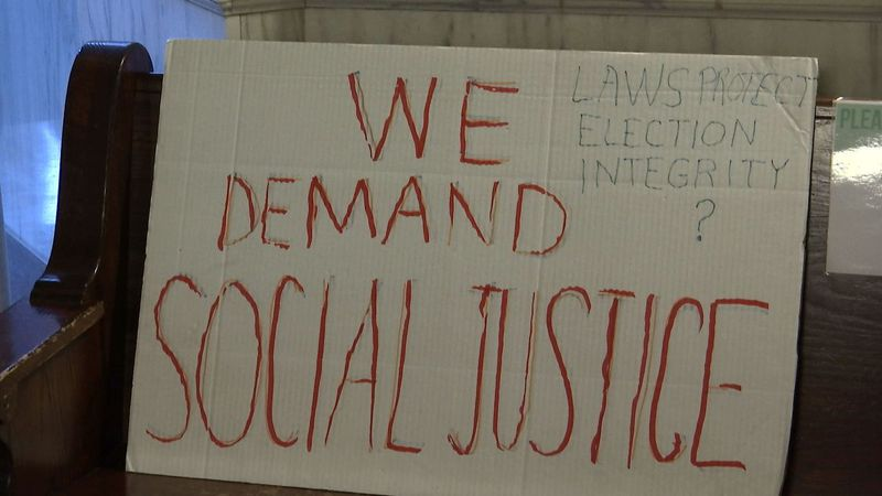 "Sign at today's press conference reads ""we demand social justice"""
