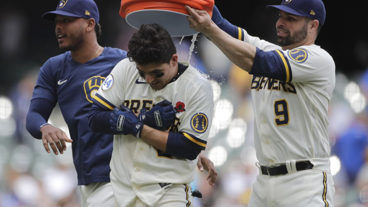 Milwaukee Brewers' Luis Urias, center, is congratulated by Manny Pina, right, and Freddy...