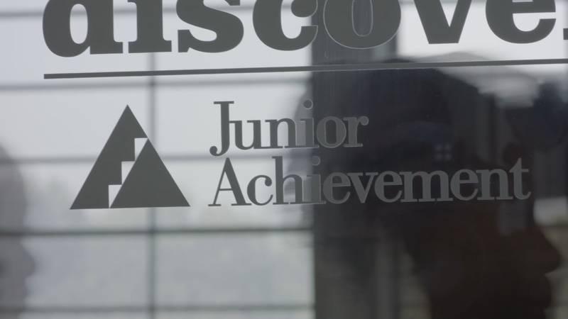 students pass by a Junior Achievement center