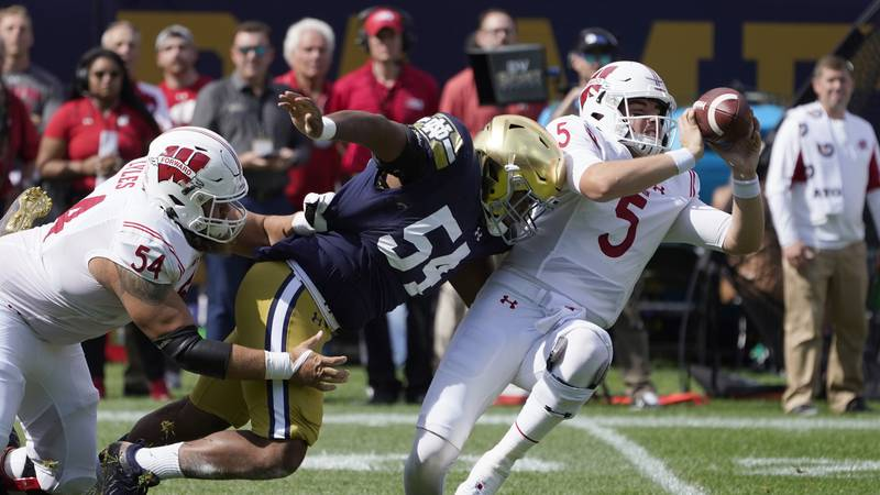 Wisconsin quarterback Graham Mertz (5) makes a two-handed pass to avoid the pressure from Notre...