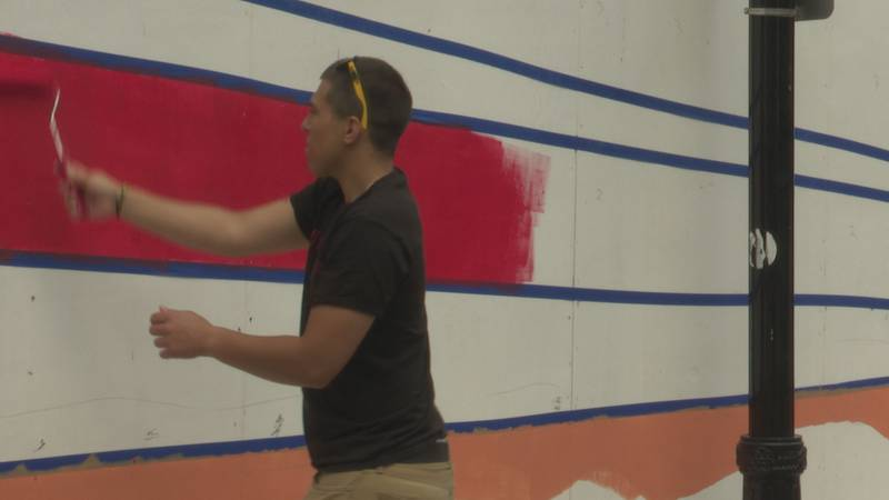 Volunteer paints mural in front of Stevens Point Opera House